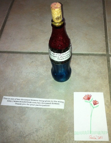 A bottle, a note and a drawing of a flower